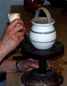 Det ubrændte lertøj dyppes i farve. Efter tørring lægges mønstret på vha. et kohorn.